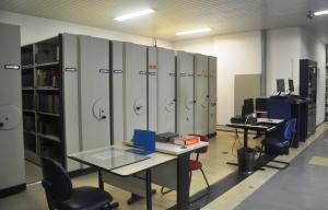 Ao fundo, acervo de referência. Em primeiro plano, mesa de consulta das coleções especiais e computadores para pesquisa.